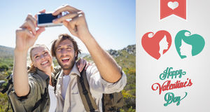 Composite image of hiking couple standing on mountain terrain taking a selfie Stock Photo