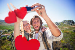 Composite image of hiking couple standing on mountain terrain taking a selfie Stock Photos