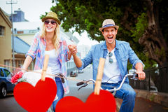 Composite image of hip young couple going for a bike ride Royalty Free Stock Photography