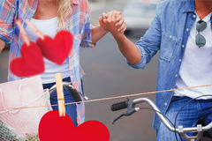 Composite image of hip young couple going for a bike ride Stock Photos