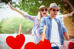 Composite image of hip young couple going for a bike ride Stock Photo