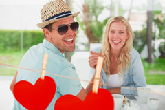 Composite image of hip young couple having coffee together Royalty Free Stock Images