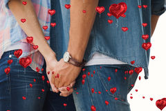 Composite image of hip young couple holding hands. Hip young couple holding hands against red heart balloons floating stock image