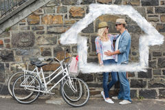 Composite image of hip young couple hugging by brick wall with their bikes Royalty Free Stock Photography