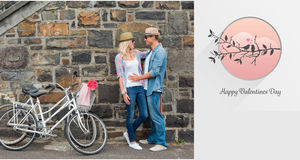 Composite image of hip young couple hugging by brick wall with their bikes Royalty Free Stock Photo