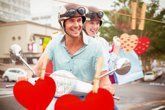 Composite image of hip young couple riding scooter with shopping bags Royalty Free Stock Photography