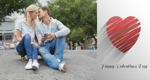 Composite image of hip young couple sitting on skateboard kissing Royalty Free Stock Photos