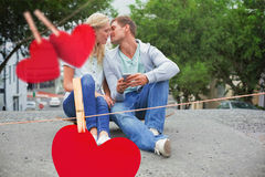 Composite image of hip young couple sitting on skateboard kissing Stock Images