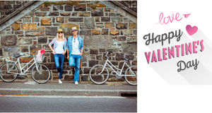 Composite image of hip young couple standing by brick wall with their bikes Stock Images