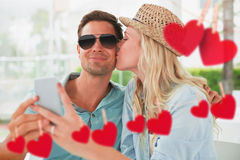 Composite image of hip young couple taking a selfie together Royalty Free Stock Photos