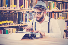 Composite image of hipster holding smoking pipe while working on typewriter Stock Photos