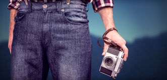 Composite image of hipster man holding digital camera Royalty Free Stock Images