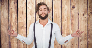 Composite image of hipster meditating arms outstretched Stock Photography