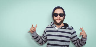 Composite image of hipster showing rock and roll hand sign Stock Photos