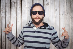 Composite image of hipster showing rock and roll hand sign Stock Photo