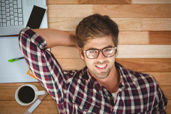 Composite image of hipster smiling while lying by laptop on hardwood floor Royalty Free Stock Image