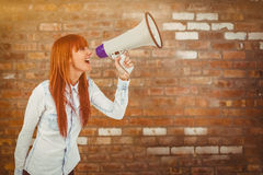 Composite image of hipster smiling woman through megaphone Stock Image