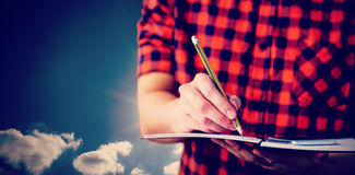 Composite image of hipster taking notes on notebooks stock image