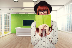Composite image of hipster woman behind a green book Royalty Free Stock Photos