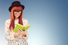 Composite image of hipster woman reading a green book Royalty Free Stock Photo