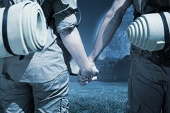 Composite image of hitch hiking couple standing holding hands on the road Stock Photos