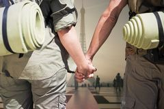 Composite image of hitch hiking couple standing holding hands on the road Stock Photo