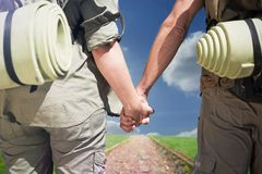 Composite image of hitch hiking couple standing holding hands on the road Royalty Free Stock Photo