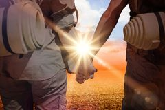Composite image of hitch hiking couple standing holding hands on the road Stock Images