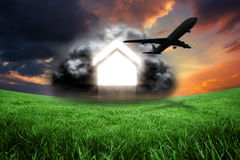 Composite image of house in grey cloud with airplane. House in grey cloud with airplane against green field under orange sky Royalty Free Stock Photos