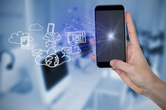 Composite image of human hand holding mobile phone against office in background Stock Image