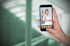 Composite image of human hand holding mobile phone against white background. Human hand holding mobile phone against white background against sterile bedroom Stock Photography