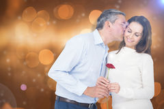 Composite image of husband kissing wife while holding rose Stock Photography