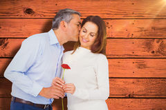 Composite image of husband kissing wife while holding rose Stock Images