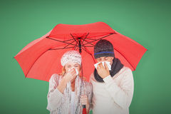 Composite image of ill couple sneezing in tissue while standing under umbrella Royalty Free Stock Image
