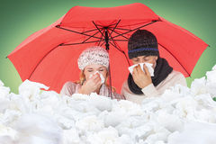 Composite image of ill couple sneezing in tissue while standing under umbrella Stock Photo