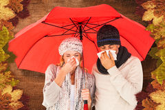 Composite image of ill couple sneezing in tissue while standing under umbrella Royalty Free Stock Images