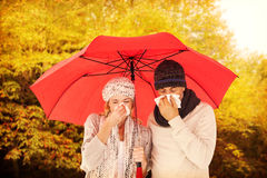 Composite image of ill couple sneezing in tissue while standing under umbrella Stock Images