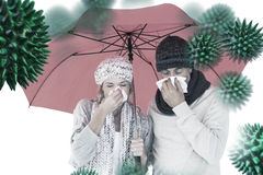 Composite image of ill couple sneezing in tissue while standing under umbrella Royalty Free Stock Photos