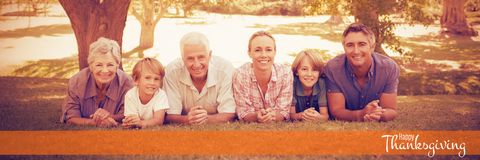 Composite image of illustration of happy thanksgiving day text greeting. Illustration of happy thanksgiving day text greeting against happy family lying on field Stock Photography