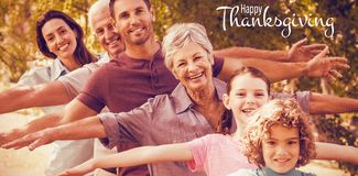 Composite image of illustration of happy thanksgiving day text greeting. Illustration of happy thanksgiving day text greeting against extended family smiling in Stock Photo