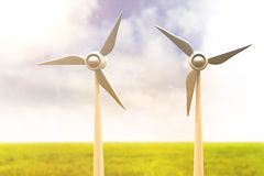 Composite image of illustration of wind mills 3d. Illustration of wind mills against blue sky over green field 3d Stock Image