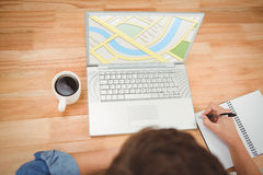 Composite image of illustrative image of map. Illustrative image of map  against hipster writing on spiral notebook by laptop at desk in office Stock Images