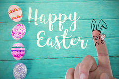 Composite image of image of fingers as easter bunny. Vector image of fingers as Easter bunny against painted easter eggs on blue wood background stock images