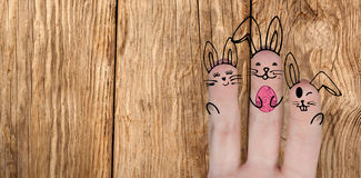 Composite image of image of fingers painted as easter bunny. Vector image of fingers painted as Easter bunny against close-up of wooden texture royalty free stock photo