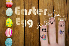 Composite image of image of fingers representing easter bunny. Vector image of fingers representing Easter bunny against painted easter eggs on table royalty free stock images