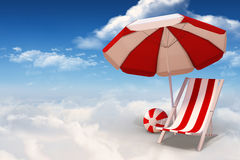 Composite image of image of sun lounger and sunshade. Image of sun lounger and sunshade against bright blue sky with clouds Stock Image