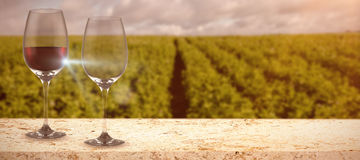 Composite image of image of a wine glass. Image of a wine glass against lettuce field Stock Photos