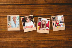 Composite image of instant photos on wooden floor. Instant photos on wooden floor against handsome men in santa hat toasting with white wine Stock Photo