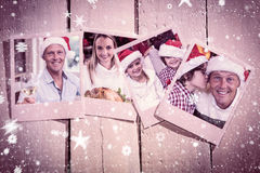Composite image of instant photos on wooden floor. Instant photos on wooden floor against handsome men in santa hat toasting with white wine Royalty Free Stock Images