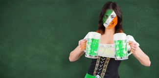 Composite image of irish girl with beer. Irish girl with beer against green chalkboard Royalty Free Stock Image